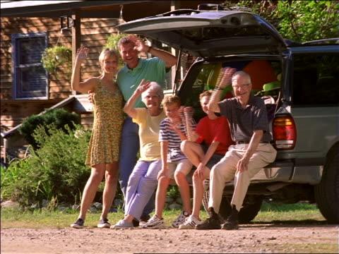stockvideo's en b-roll-footage met portrait man, woman, two boys, senior man + woman posing + waving open hatch of suv - hatch