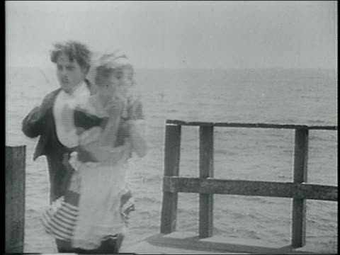 stockvideo's en b-roll-footage met b/w 1915 man woman upset about something on edge of pier - 1915