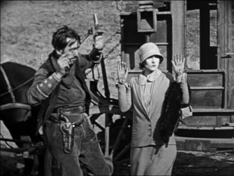 vidéos et rushes de b/w 1924 man + woman with hands in air during stagecoach hold-up / man gestures to boot / feature - 1924