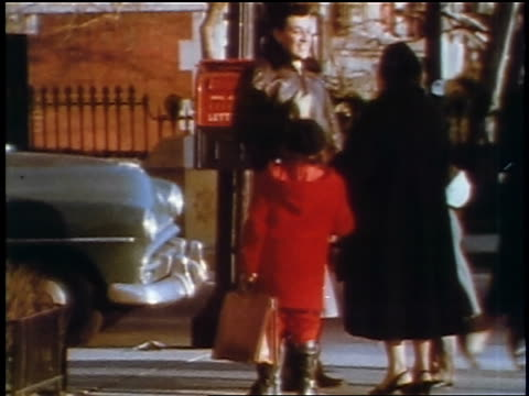 1957 man, woman + young girl standing on street corner talking / feature