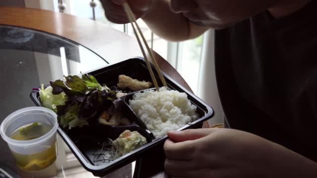 vídeos de stock, filmes e b-roll de trabalho duro no computador e comendo comida japonesa em cima da mesa. - almoço