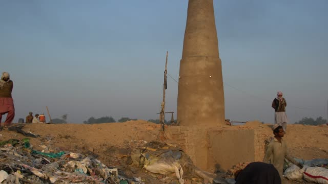 man working around the big chimney of a local brick kiln factory punjab, pakistan - pakistan stock videos & royalty-free footage