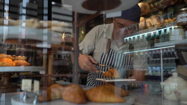 mann, der in einer bäckerei arbeitet und ein croissant mit zange schnappt - fleischzange stock-videos und b-roll-filmmaterial