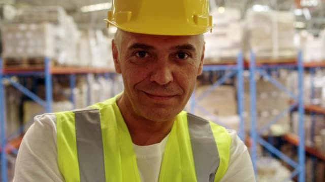 mann arbeitet in einem lagerhaus  - schutzhelm stock-videos und b-roll-filmmaterial