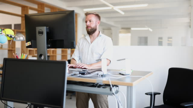 man working at ergonomic standing desk in office - standing stock videos & royalty-free footage