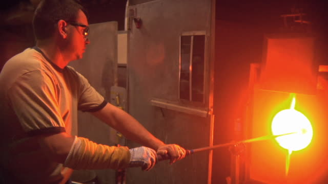 MS WS Man working at glass blowing factory / Windsor, Vermont, USA