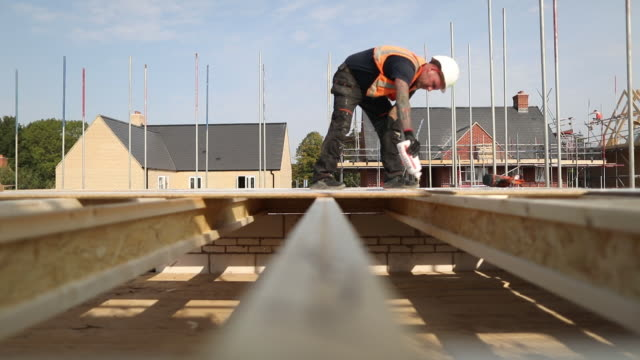 man working at persimmon and charles church new housing construction site, in towcester, northamptonshire, u.k., england, on wednesday, september 16,... - building exterior stock videos & royalty-free footage