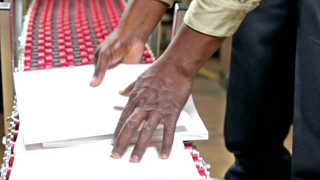 Man working at printers packing catalogs