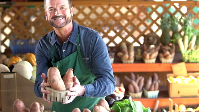 man working at produce stand - potato stock videos & royalty-free footage