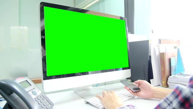Man working both Smartphone and Computer with green screen