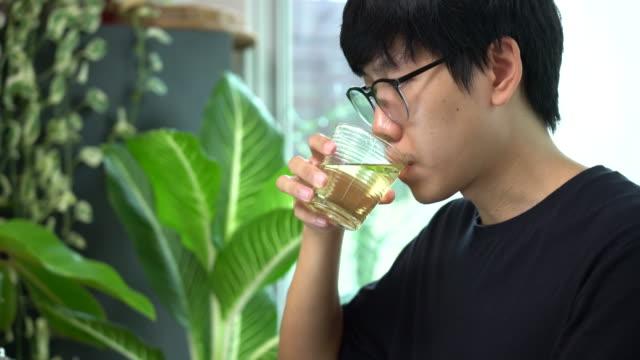 vidéos et rushes de homme travaillant de la maison buvant le thé vert dans le verre - hot desking