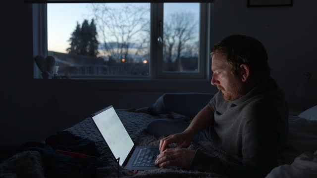 man working from home on his laptop in the evening. - bed stock videos & royalty-free footage