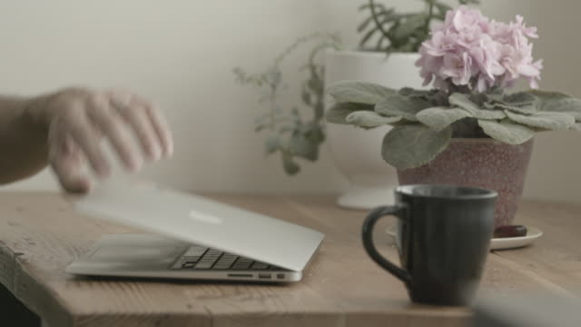 man working from home sits down with coffee - cup stock videos & royalty-free footage