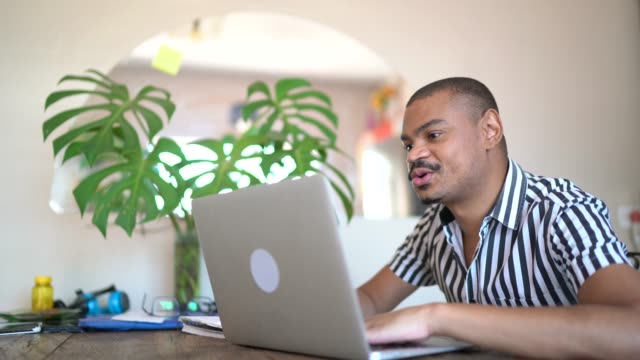 vidéos et rushes de homme travaillant de la maison, utilisant l'ordinateur portatif dans la cuisine - au loin