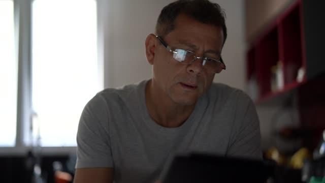 uomo che lavora da casa - uomini maturi video stock e b–roll