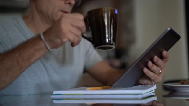 vídeos de stock, filmes e b-roll de homem que trabalha de casa ao tomar o pequeno almoço - manhã