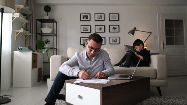 stockvideo's en b-roll-footage met mens die van huis met laptop tijdens quarantaine werkt. - familie met één kind