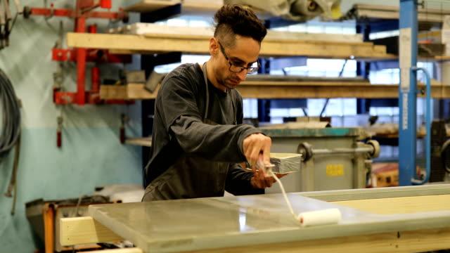 uomo che lavora in un laboratorio di produzione di mobili in cemento - sigillante video stock e b–roll