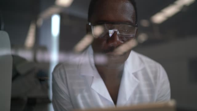 vídeos de stock, filmes e b-roll de homem que trabalha em um laboratório, usando a tabuleta digital - concentração