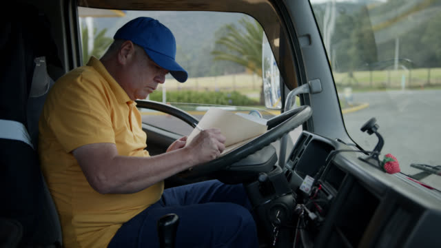 man working in a truck filling in a form before delivering a product to customer - heavy goods vehicle stock videos & royalty-free footage