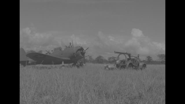 man working in cockpit of airplane / young man hanging up clothes to dry / small truck pulling caisson with bomb as man walks alongside / three men... - pacific war stock videos and b-roll footage