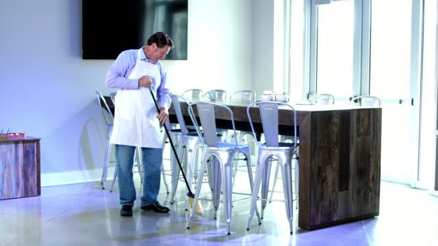 床を掃除するコーヒー ショップで働く男 - 掃く点の映像素材/bロール