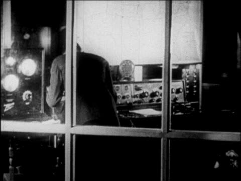 b/w 1927 rear view man working in control room in radio station / newsreel - anno 1927 video stock e b–roll