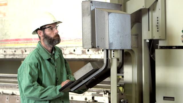 man working in factory setting controls on machinery - laboratorio riparazioni video stock e b–roll