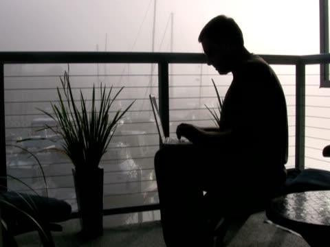 man working in fog, closes laptop, walks past camera - hot desking stock videos & royalty-free footage