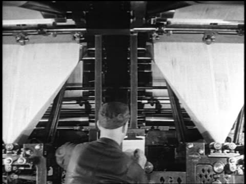 vidéos et rushes de b/w 1919 man working in front of newspaper printing presses / newsreel - 1910 1919