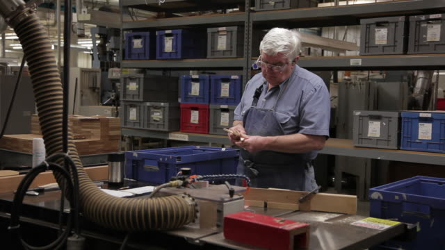 ms man working in guitar factory, making notation in log / nazareth, pennsylvania, usa - produktionslinjearbetare bildbanksvideor och videomaterial från bakom kulisserna