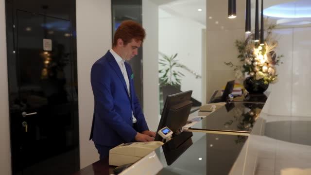 vídeos y material grabado en eventos de stock de hombre que trabaja en el hotel en la recepción - hospitalidad