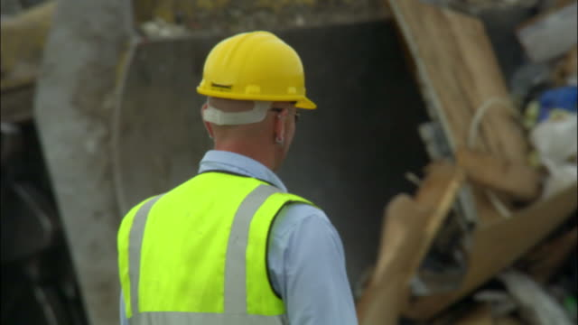 cu, man working in landfill site, rear view, ardley, oxfordshire, united kingdom - oxfordshire stock videos & royalty-free footage