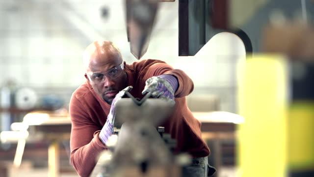 mann arbeitet in metallverarbeitung shop - schutzbrille stock-videos und b-roll-filmmaterial