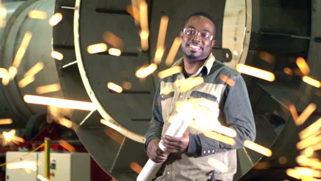 vidéos et rushes de homme travaillant dans l'atelier de fabrication de métal, avec le soudeur - metal