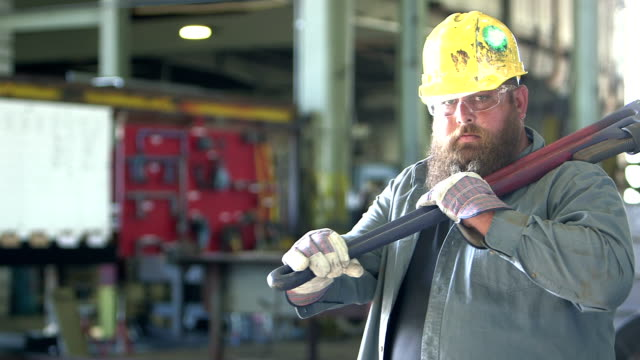 Man working in repair shop carrying giant wrench