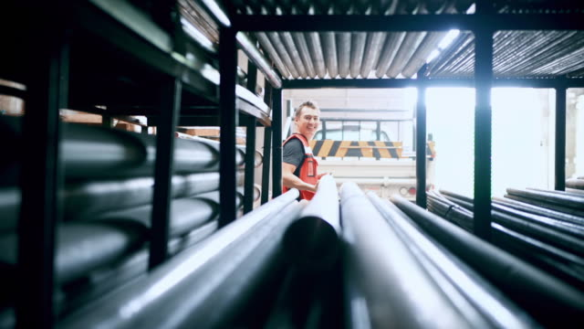man working in tubing warehouse - steel stock videos & royalty-free footage