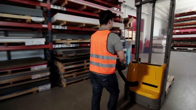 mann, der im lager mit einem palettenwagen arbeitet - hubwagen stock-videos und b-roll-filmmaterial