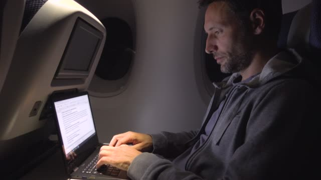 man working late during a flight. business casual trip - air vehicle stock-videos und b-roll-filmmaterial