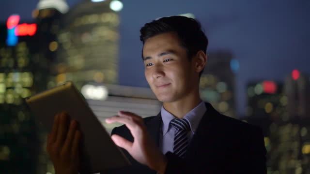 vídeos y material grabado en eventos de stock de ms ts man working on a digital tablet at night - negocio global
