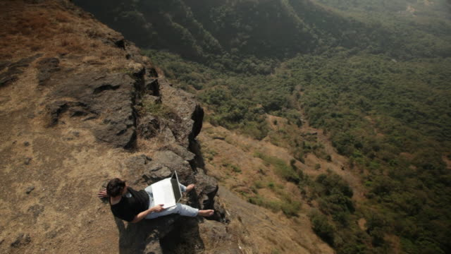 man working on a laptop on the cliff of mountain  - 辺縁部点の映像素材/bロール