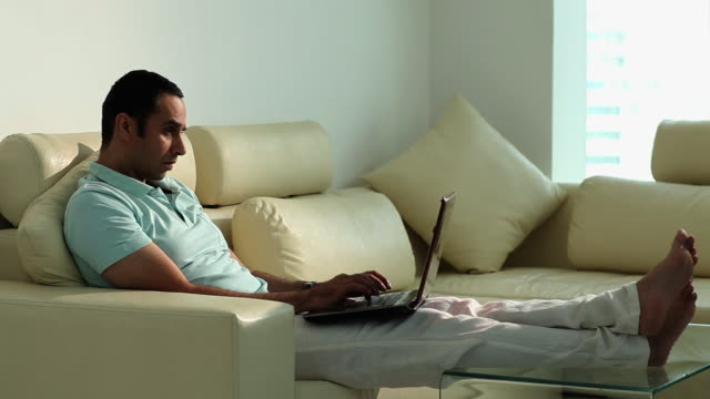 man working on a laptop  - legs crossed at ankle stock videos and b-roll footage