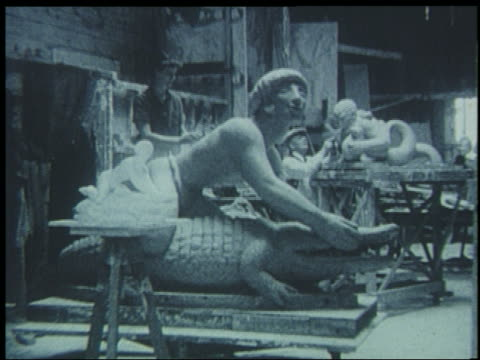 b/w 1939 man working on alligator man statue in workshop for world's fair - getönt stock-videos und b-roll-filmmaterial