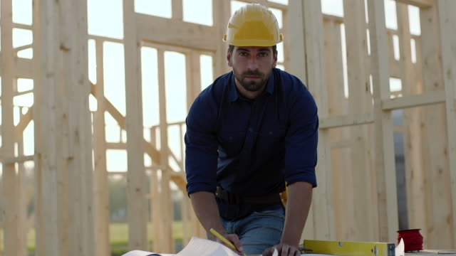 Man working on blueprints at construction site