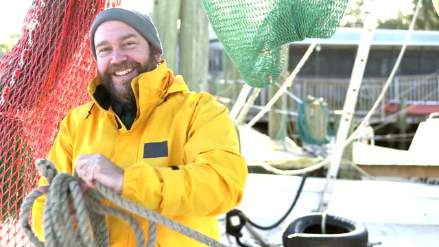 man working on commercial fishing boat coiling a rope - fisherman stock videos & royalty-free footage