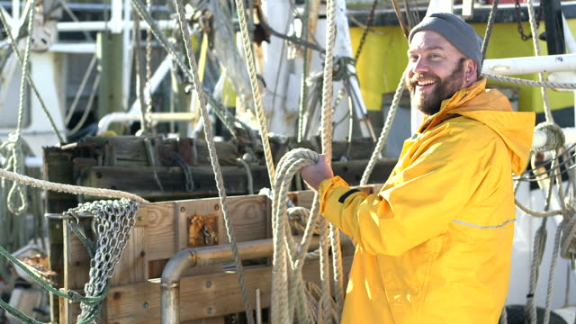 man working on commercial fishing boat coiling a rope - fisherman stock videos and b-roll footage