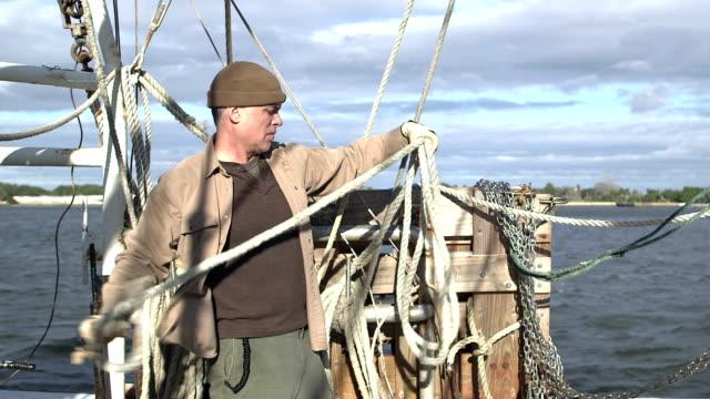 vídeos y material grabado en eventos de stock de hombre trabajando en barco de pesca comercial que arrolla una cuerda - gorro de lana