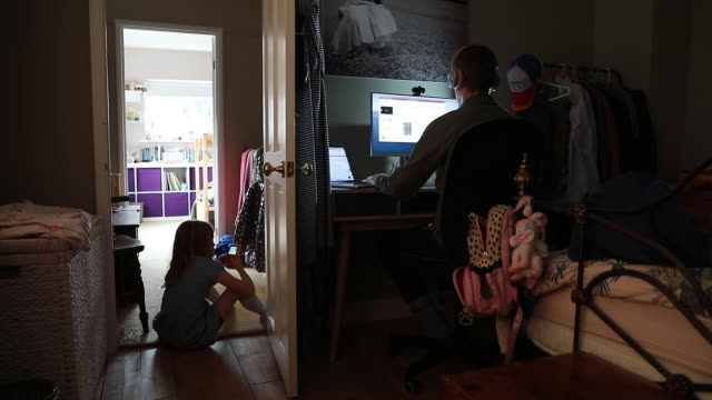 man working on computer in bedroom while daughter playing on smart phone amid coronavirus pandemic in guildford, surrey, uk on friday, september 11,... - convenience stock videos & royalty-free footage