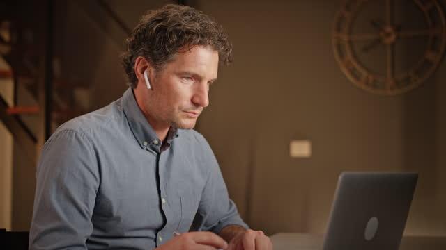 vídeos de stock, filmes e b-roll de homem trabalhando em seu laptop em casa à noite - audio available