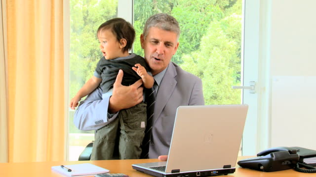 man working on laptop and phoning while holding baby / cape town, western cape, south africa - genderblend video stock e b–roll